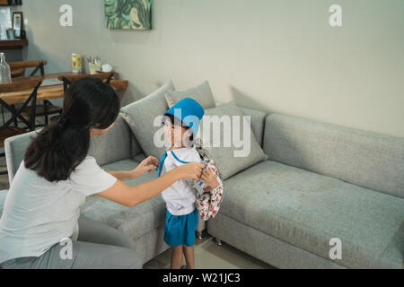 mom help her little girl to put a backpack on before going to school - Stock Image