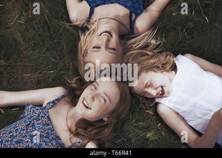 Portrait happy sisters laying in grass - Stock Image
