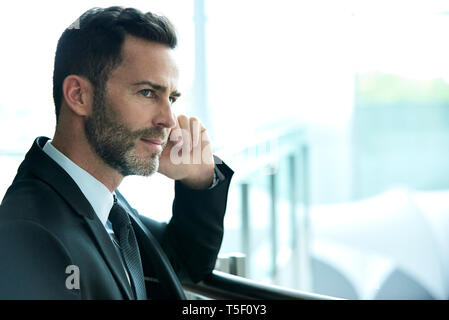 Thoughtful businessman standing in hotel lobby - Stock Image