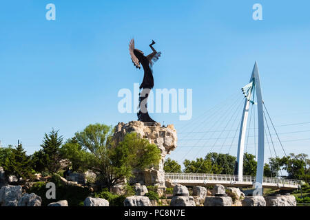 Keeper of the Plains, a steel sculpture by Blackbear Bosin. Wichita, Kansas, USA. Visible is a pedestrian suspension bridge. - Stock Image