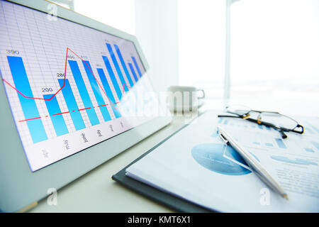 Image of workplace with paper and electronic documents on desk - Stock Image