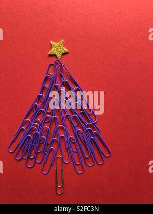 Creative Christmas concept. Christmas tree made from purple paper clips topped with a gold star on a red background with copy space - Stock Image