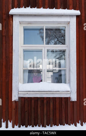 Finland, Kuopio, little girl looking out of window of farmhouse in winter - Stock Image