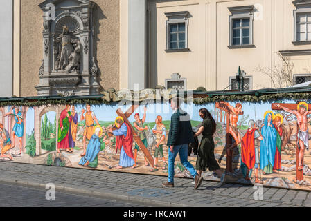 Vienna Easter, view of a young couple walking past a colorful illustration of The Passion Of Christ beside the Schottenkirche in the centre of Vienna. - Stock Image