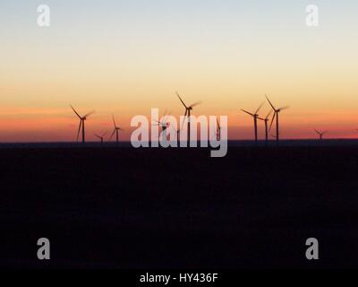 Wind Turbines In Sea Against Sky During Sunset - Stock Image