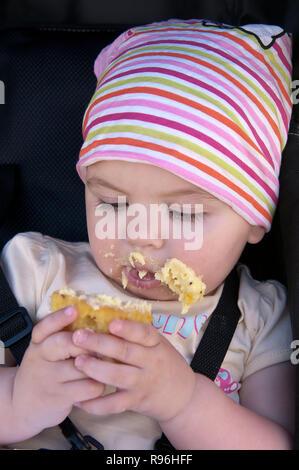 BW8DBF todler enjoying eating a cake and making a mess - Stock Image