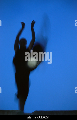 Silhouette of female dancer jumping at twilight - Stock Image