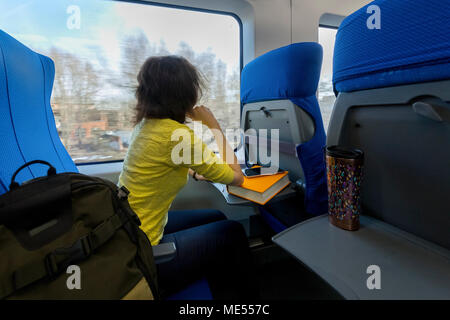 young attractive woman loking in the window during traveling in train - Stock Image
