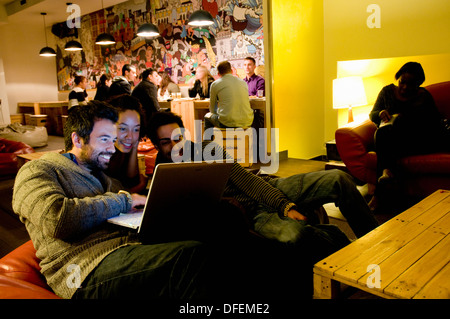 Guests at Yes! Lisbon Hostel in Lisbon get togther in the common room to socialise and check emails using a laptop. - Stock Image