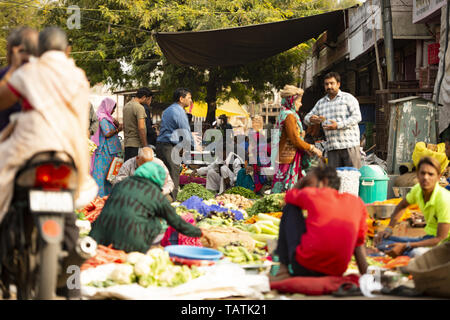 Customers and traders in a street market in Jaipur. Jaipur is the capital and the largest city of the Indian state of Rajasthan, India. - Stock Image