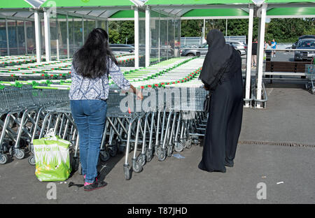 Two ladies with supermarket trolleys, ASDA car park Crossharbour, London Borough of Tower Hamlets. - Stock Image