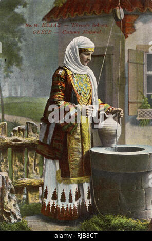 Greek woman standing at a well in national costume. - Stock Image