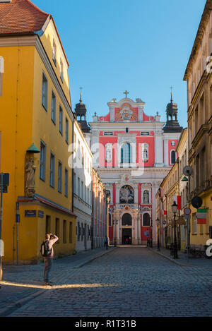 Man taking photo, in a street in Poznan Old Town a solo travel photographer takes a photograph of the Baroque facade of St Stanislaus Church, Poland. - Stock Image