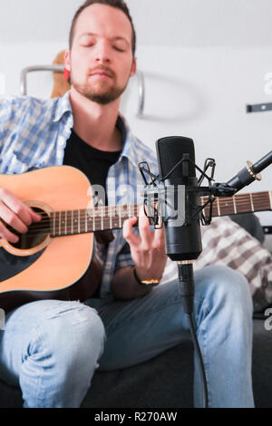 young man recording his acoustic guitar while sitting on a sofa - Stock Image