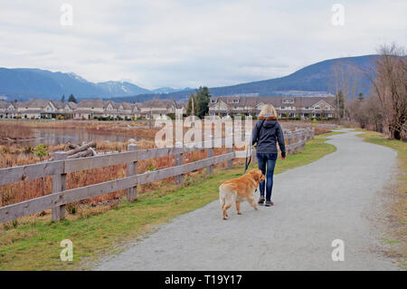 Blonde Woman walking her dog along a gravel pathway in Blakeburn Lagoons Regional Park, Port Coquitlam, B., C., Canada. - Stock Image
