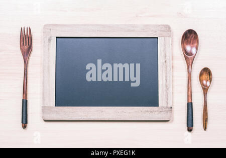 Blackboard With Wooden Frame And Copy Space For A Menu Next To A Wooden Fork And Two Spoons - Stock Image