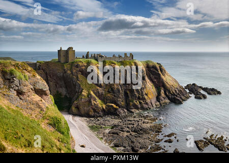 Dunnottar Castle Medieval clifftop ruins in sun from cliff above rocks and pebble beach of Old Hall Bay North Sea near Stonehaven Scotland UK - Stock Image