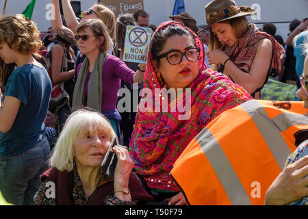 London, UK. 19th April 2019. People outside the police cordon at Oxford Circus at Extinction Rebellion's Sea of Protest support those inside the cordon protecting the pink yacht Berta Cacares. Police were trying to persuade protesters to leave by threatening them with arrest and cutting off those who were locked on around the bottom of the yacht. There were a number of arrests of protesters who refused to leave. A few tried to get the large crowd to protect the yacht, but XR organisers persuaded them not to physically oppose the police action. Peter Marshall/Alamy Live News - Stock Image