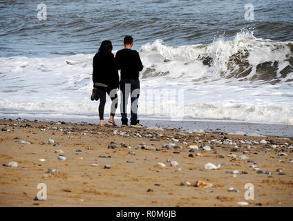 A young couple enjoy each other's company as they walk along a Norfolk beach trying to avoid the wash from the choppy sea's rashing waves. - Stock Image