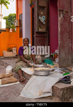 Vertical view of a lady making paratha on her doorstep in Fort Kochi, India. - Stock Image