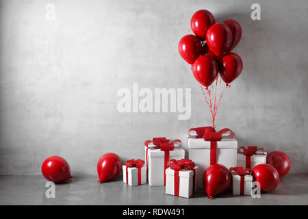 Red balloons and white gift boxes on concrete wall background - Stock Image