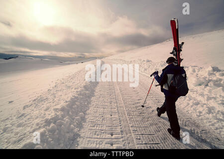 Rear view of man carrying skis while walking on snowy field - Stock Image