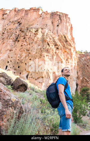 Los Alamos park with man hiking walking on Main Loop trail path in Bandelier National Monument in New Mexico during summer by canyon cliff - Stock Image