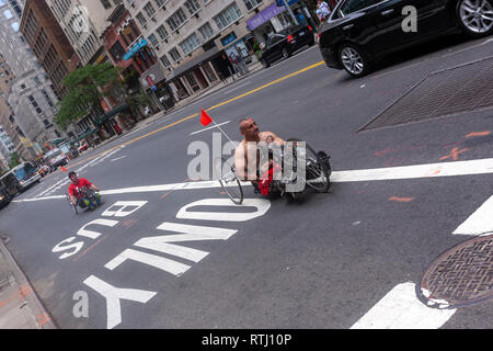 Two men with a tadpole recumbent tricycle along a only bus lane in  E 57th St, Manhattan, New York, USA - Stock Image