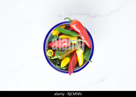 Capsicum annuum. Chillies in an enamel bowl on a marble surface. - Stock Image