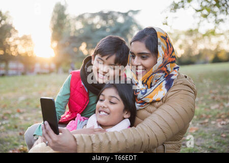 Muslim mother in hijab taking selfie with camera phone in autumn park - Stock Image