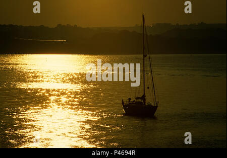 A yacht moored in Brixham,  Torbay in the sunset - Stock Image