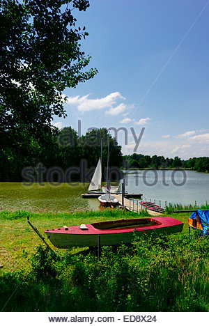 A couple prepares to sail a small boat on the lake at Haselünne by the Ems River in Lower Saxony near the Dutch - Stock Image