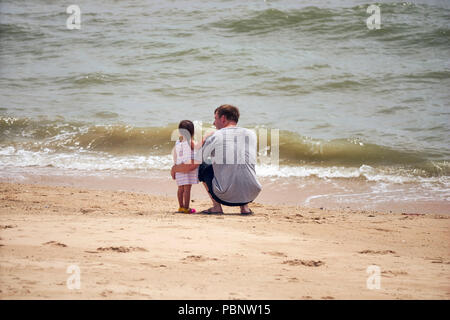 Father and child on the beach. - Stock Image