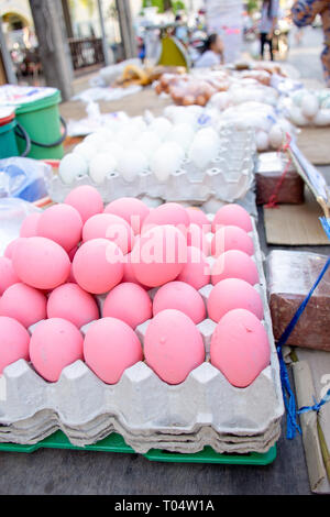 Chicken eggs painted pink for sale on market stall, Phuket, Thailand. - Stock Image