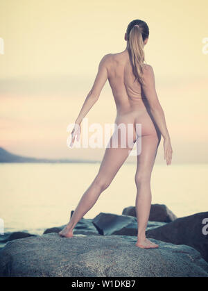 Happy sporty naked female doing aerobics at ocean quay - Stock Image