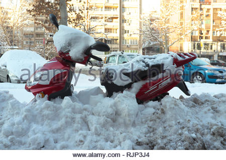 A scooter is partially submerged under recent heavy snowfall in the city of Novi Sad, Vojvodina, Serbia. - Stock Image