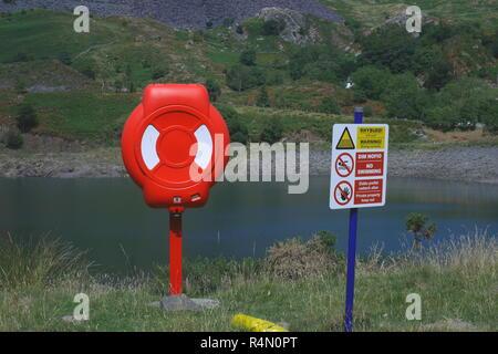Life ring and warning sign next to a lake in Snowdonia, North Wales, Inited Kingdom - Stock Image