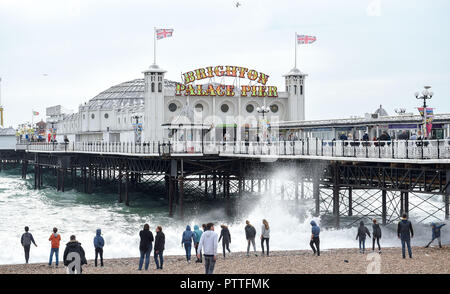 Brighton UK 11th October 2018 - Visitors watch the waves roll onto Brighton beach by the Palace Pier as storms with high winds are forecast to hit some parts of Britain tomorrow Credit: Simon Dack/Alamy Live News - Stock Image