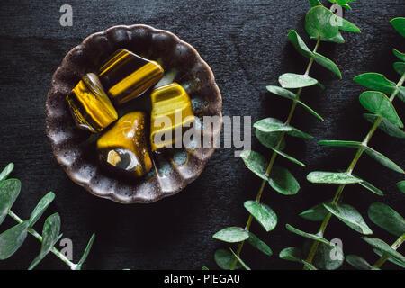 Eucalyptus and Tiger's Eye on Black Table - Stock Image
