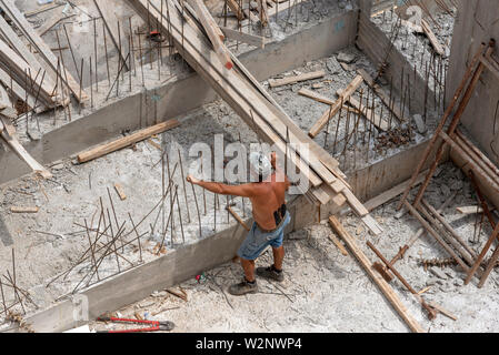 Crete, Greece. June 2019. A builder on site working with recycled  wooden planks - Stock Image