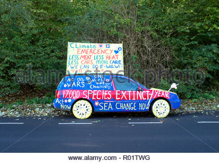 Nailsworth, Gloucestershire, UK. 31st October, 2018. A brightly painted car is covered in messages relating to global climate change and species extinction. Much has been highlighted recently regarding various issues that will affect much of our world. The car was parked in a lay-by opposite a fuel station adjacent to the A46 road in Nailsworth, Gloucestershire, UK., 31st October 2018. Credit Phil Wills/Alamy Live News. - Stock Image