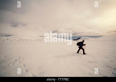 Side view of skier walking on snow against cloudy sky - Stock Image