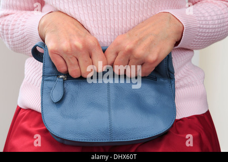 Insecure senior woman sitting and tightly clutching a handbag on her lap with two hands close to her for security. England, UK, Britain - Stock Image