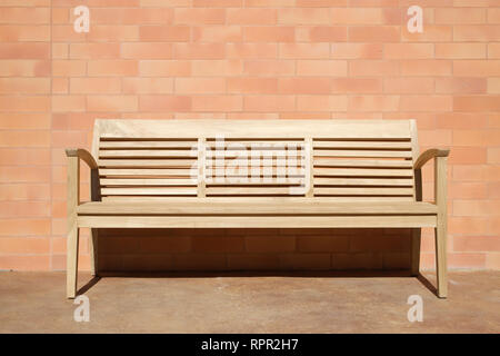 Wooden Bench Set Against Brick Wall - Stock Image