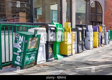 ASHEVILLE, NC, US-2/3/19: A line of vending machines for newspapers and other literature on the sidewalk in front of the city library. - Stock Image