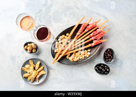 Italian antipasti. Grissini with wine glasses, prosciutto di parma and roasted almonds, with olives and artichokes, shot from the top with copy space - Stock Image