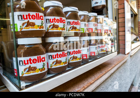 Glass jars of the Italian hazenut spread Nutella for sale from a shop window. - Stock Image