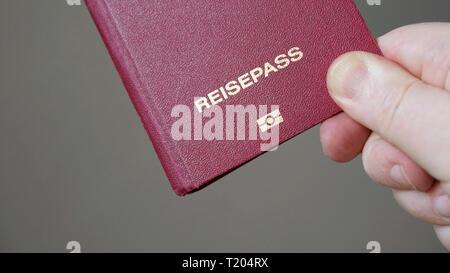 Reisepass is German for passport - hand holding biometric e-passport from Germany - Stock Image