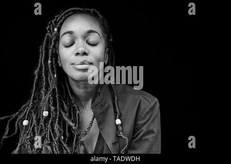 Portrait of woman with dreadlocks in front of black background - Stock Image