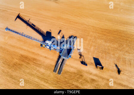 Grain bulk storage elevator site with mechanical loader processing tonnes of wheat and other grains in aerial overhead top down view. - Stock Image